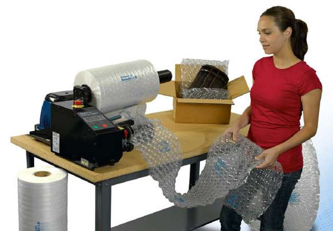 Factory worker using sealed air void filling machine for products in packaging boxess